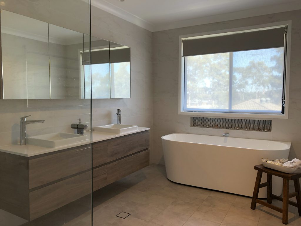 Gorgeous free standing bath with timber wall hung vanity and large mirrored shaving cabinet - Bathroom Renovation by Master Bathrooms & Kitchens